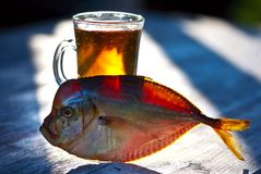 Smoked fish on the wooden table, vomer, beer Royalty Free Stock Images