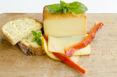 Smoked full fat cheese 2. Smoked full fat cheese, a couple of slices and piece, healthy homemade bread, fresh red pepper and fresh, green basil leaves on grunge Stock Photos