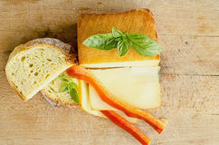 Smoked full fat cheese 5. Smoked full fat cheese, a couple of slices and piece, healthy homemade bread, fresh red pepper and fresh, green basil leaves on grunge Royalty Free Stock Image
