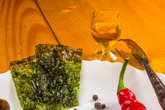 Smoked garfish with lime, Basil, green onions, chili, nori chips, spices, olive oil in a white ceramic dish, on a wooden table. Still life - smoked garfish with royalty free stock photos
