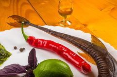 Smoked garfish with lime, Basil, green onions, chili, nori chips, spices, olive oil in a white ceramic dish, on a wooden table. Still life - smoked garfish with royalty free stock image