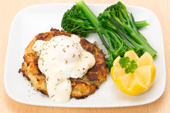 Smoked haddock fishcake dinner with a poached egg. Homemade smoked haddock fishcake dinner with a poached egg, brocolli and diced pototoes - studio shot Royalty Free Stock Image