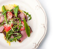 Smoked ham and arugula salad on the white ceramic plate Royalty Free Stock Photos