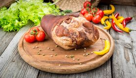 Smoked ham hock with herbs and spices on wooden plate. Smoked ham with herbs and spices on a wooden table Stock Images