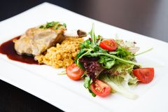 Smoked ham hock. With herbs, tomatoes and spices on white plate Stock Photography