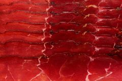 Smoked ham. Italian speck red meat slices  on white background. Prosciutto beaf meat slices as texture . Royalty Free Stock Images