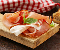 Smoked ham jamon (Parma) with basil leaves Stock Photography