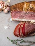 Smoked ham, and jerky on table with garlic herbs, Natural product from organic farm, produced by traditional methods. Smoked ham on table with garlic and biltong royalty free stock photography