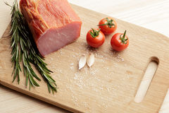 Smoked Ham with mushrooms, tomato, garlic and herbs. Piece of smoked meat with some fresh mushrooms, tomato, garlic and herbs on wooden background. rustic style stock image