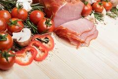 Smoked Ham with mushrooms, tomato, garlic and herbs. Piece of smoked Ham with some fresh mushrooms, tomato, garlic and herbs on wooden background. rustic style Stock Photos