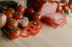 Smoked Ham with mushrooms, tomato, garlic and herbs. Piece of smoked Ham with some fresh mushrooms, tomato, garlic and herbs on wooden background. rustic style Stock Photo