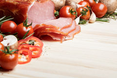 Smoked Ham with mushrooms, tomato, garlic and herbs. Piece of smoked Ham with some fresh mushrooms, tomato, garlic and herbs on wooden background. rustic style Royalty Free Stock Images