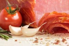 Smoked Ham with mushrooms, tomato, garlic and herbs. Piece of smoked Ham with some fresh mushrooms, tomato, garlic and herbs on wooden background. rustic style Royalty Free Stock Photos