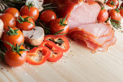 Smoked Ham with mushrooms, tomato, garlic and herbs. Piece of smoked Ham with some fresh mushrooms, tomato, garlic and herbs on wooden background. rustic style royalty free stock image