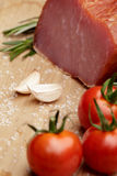 Smoked Ham with mushrooms, tomato, garlic and herbs. Piece of smoked Ham with some fresh mushrooms, tomato, garlic and herbs on wooden background. rustic style stock photography