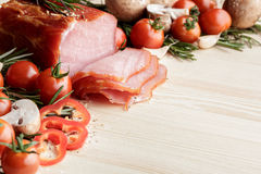 Smoked Ham with mushrooms, tomato, garlic and herbs. Piece of smoked Ham with some fresh mushrooms, tomato, garlic and herbs on wooden background. rustic style royalty free stock photo