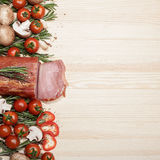 Smoked Ham with mushrooms, tomato, garlic and herbs. Piece of smoked Ham with some fresh mushrooms, tomato, garlic and herbs on wooden background. space for text royalty free stock photography