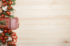 Smoked Ham with mushrooms, tomato, garlic and herbs. Piece of smoked Ham with some fresh mushrooms, tomato, garlic and herbs on wooden background. space for text Stock Image