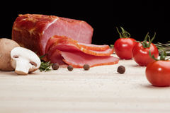 Smoked Ham with mushrooms, tomato, garlic and herbs. Piece of smoked Ham with some fresh mushrooms, tomato, garlic and herbs on wooden Board on black background stock images