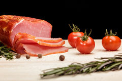 Smoked Ham with mushrooms, tomato, garlic and herbs. Piece of smoked Ham with some fresh mushrooms, tomato, garlic and herbs on wooden Board on black background royalty free stock image