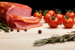 Smoked Ham with mushrooms, tomato, garlic and herbs. Piece of smoked Ham with some fresh mushrooms, tomato, garlic and herbs on wooden Board on black background royalty free stock photography