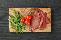 Smoked ham prsut with cherry tomatoes and arugula Royalty Free Stock Photo