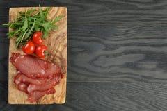 Smoked ham prsut with cherry tomatoes and arugula Royalty Free Stock Image