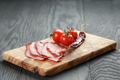 Smoked ham prsut with cherry tomatoes and chili Stock Photos
