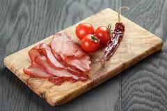 Smoked ham prsut with cherry tomatoes and chili Stock Photography