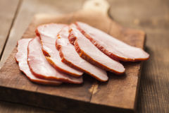 Smoked ham. Sliced smoked ham on wooden board stock photos