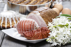 Smoked ham on squared napkin, on wooden table. Stock Photos