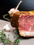 Smoked ham on a stone table with addition of fresh aromatic herbs and spices. Natural product from organic farm, produced by. Traditional methods, free space stock photography