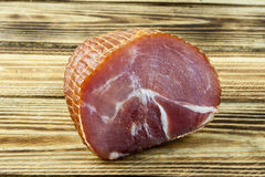 Smoked ham on a wooden background Stock Image