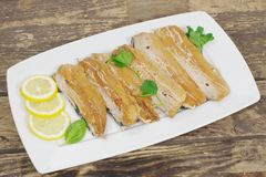 Smoked herring fillets. With lemon and basil Royalty Free Stock Image