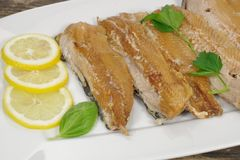 Smoked herring fillets. With lemon and basil Stock Image