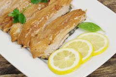 Smoked herring fillets. With lemon and basil Royalty Free Stock Photos