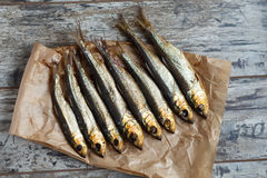 Smoked herring on a paper and wooden table Royalty Free Stock Image