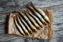Smoked herring on a paper and wooden table Royalty Free Stock Images