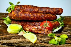 Smoked home sausages with seasoned salad. Tasty smoked sausages with fields salad ready for consumption Stock Image