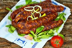 Smoked home sausages with seasoned salad. Tasty smoked sausages with seasoned salad ready for consumption Stock Photography