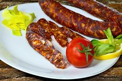 Smoked home sausages with seasoned salad. Tasty smoked sausages with seasoned salad ready for consumption Royalty Free Stock Image