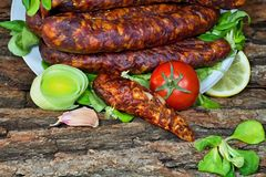Smoked home sausages with seasoned salad. Tasty smoked sausages with seasoned salad ready for consumption Stock Images