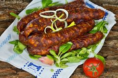 Smoked home sausages with seasoned salad. Tasty smoked sausages with seasoned salad ready for consumption Stock Image