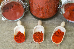 Smoked hot paprika, sweet paprika and chopped papr. Ika in wooden scoops and jars on background stock photo