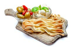 Smoked and Italian mozzarella cheese, olives, pepper on wooden cutting board. White background Stock Photography