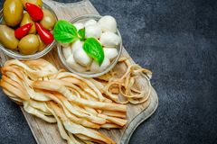 Smoked and Italian mozzarella cheese, olives, pepper on wooden cutting board. Dark concrete background Stock Photo