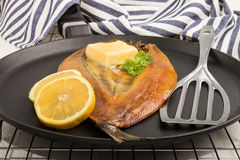 Smoked kipper with lemon, butter and parsley on a pan. Scottish smoked kipper with lemon, butter and parsley on a pan Royalty Free Stock Images