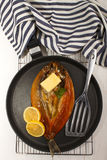 Smoked kipper with lemon, butter and parsley on a pan. Scottish smoked kipper with lemon, butter and parsley on a pan Royalty Free Stock Photos