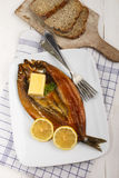 Smoked kipper with lemon, butter and parsley on a plate. Scottish smoked kipper with lemon, butter and parsley on a plate Stock Photography