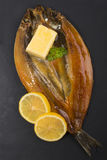 Smoked kipper with lemon, butter and parsley on slate. Scottish smoked kipper with lemon, butter and parsley on slate Royalty Free Stock Photos
